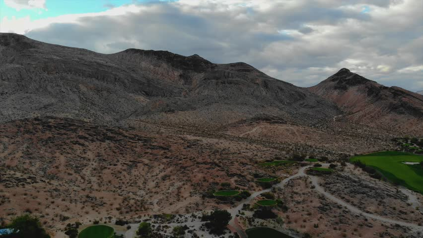 4K resolution, aerial drone at 24 frames per second (24fps / 24 fps) over Nevada mountains in Red Rock neighborhood of Las Vegas with cloudy skies (sped up / fast forward speed, upward motion) | Shutterstock HD Video #1028344499