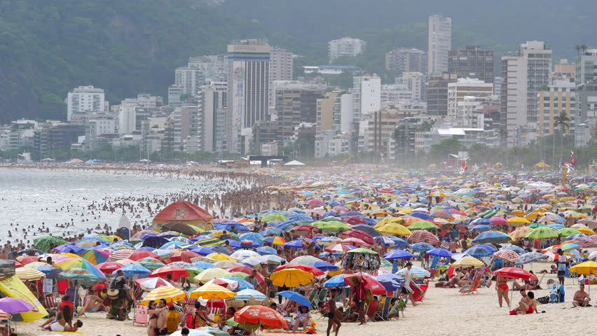 Rio de Janeiro, Brazil - December 31, 2018: View of Ipanema Beach showing people and colourful umbrellas on a summer day in Rio de Janeiro, Brazil.