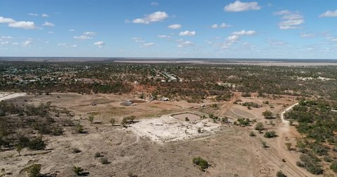 Dirt grounds of red soil in Australian outback around Lightning ridge opal mining town with arid dry climate on flat plain.