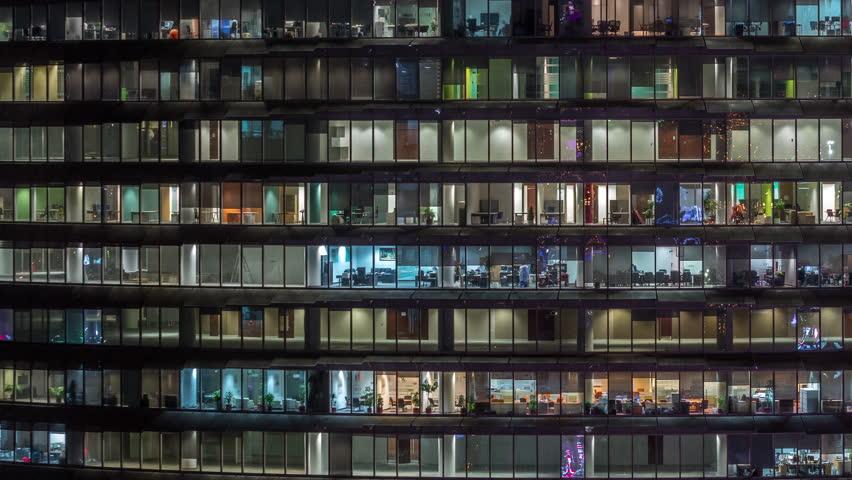 Working evening in glass business centre office building with numerous offices with glass walls and illuminated windows timelapse. People sitting at desks | Shutterstock HD Video #1028367179