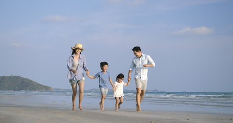 Asian family running with happy emotion at Beach together. Slow motion. Family, Holiday and Travel concept.