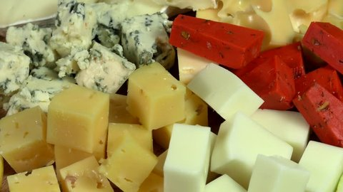 Cheese plate close-up with several varieties of fruit and honey cheese.