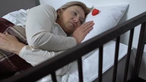 Sick woman holding little toy heart, organ transplantation, concept of hope