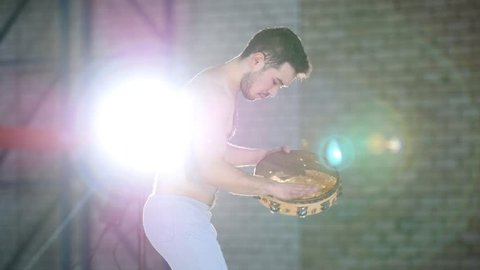 A man playing tambourine in a bright room