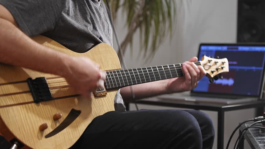 Close up of professional musician recording electric guitar in digital studio at home.  He is surrounded with instruments and midi controller. Music production concept.    Shutterstock HD Video #1028425739