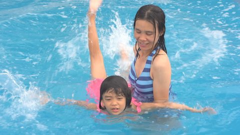 Family funny concept, mother training daughter swimming in swimming pool, child kid family time happy in vacation summer, Asian kids children happy for learning with mother in pool