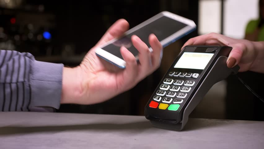 Close-up shot of man applies his cellphone to terminal performing successful contactless payment. | Shutterstock HD Video #1028450189