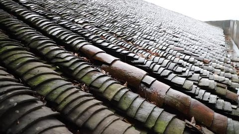 rain falls on traditional Chinese house roof of tiles: closeup