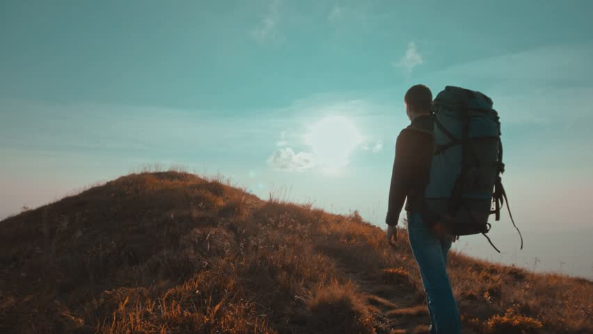 The male with a tourist backpack walking on the mountain   Shutterstock HD Video #1028487059