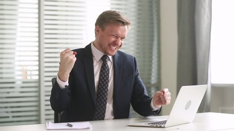 Happy motivated businessman winner use laptop looking at computer feel overjoyed reading great online news get promoted rewarded celebrate business success, professional achievement, good work result