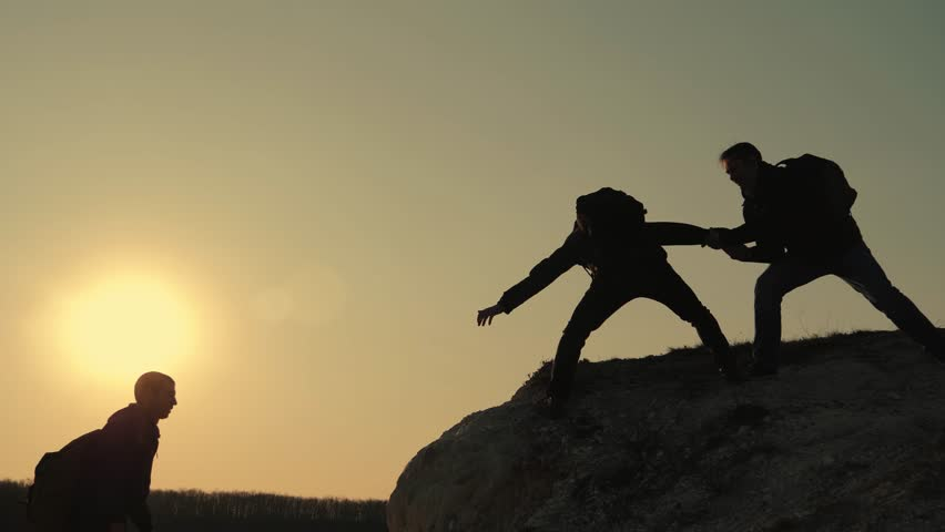 Silhouettes of tourists climbing mountain cliffs against the backdrop of a sunset, helping each other's hand. Help in the mountains and teamwork in hiking. Teamwork concept. | Shutterstock HD Video #1028518109