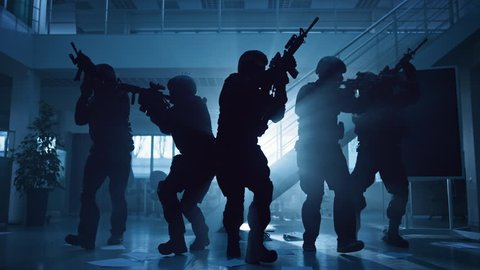 Masked Fireteam of Armed SWAT Police Officers Storm a Dark Seized Office Building with Desks and Computers. Soldiers with Rifles Move Forwards and Cover Surroundings.