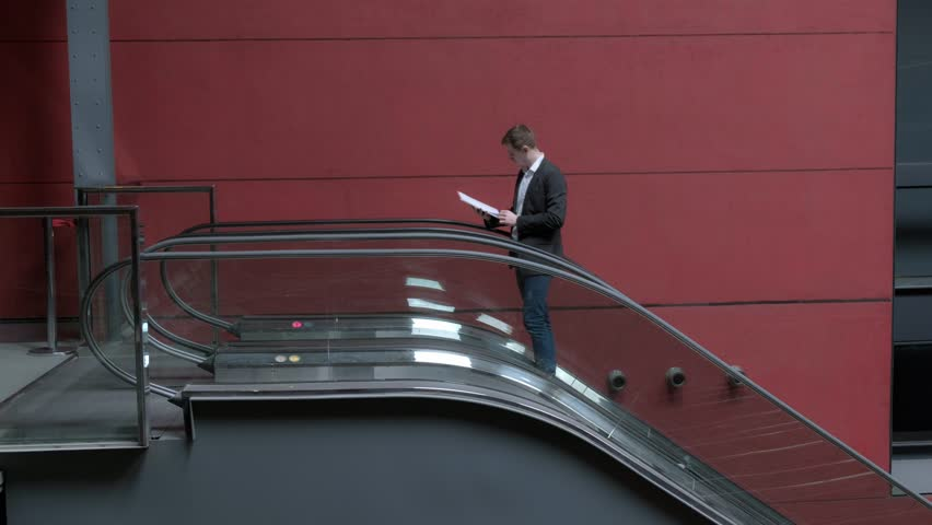 Young man moving on the escalator. businessmen. office worker. 4 K Video     Shutterstock HD Video #1028560259