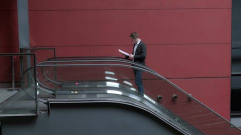 Young man moving on the escalator. businessmen. office worker. 4 K Video