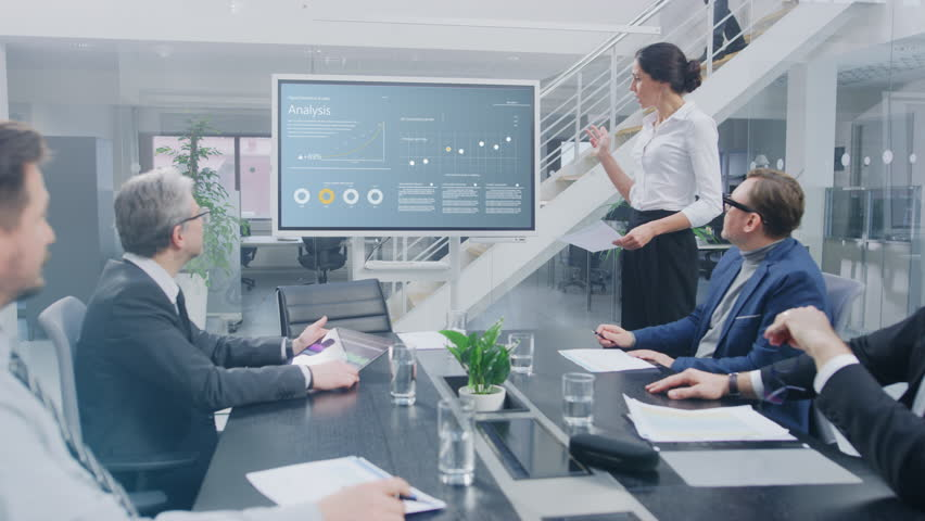 In the Corporate Meeting Room: Female Analyst Uses Digital Interactive Whiteboard for Presentation to a Board of Executives, Lawyers, Investors they Applaud. Screen Shows Company Growth Data