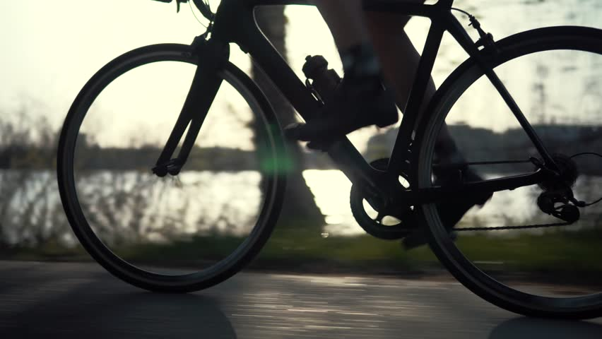 Cyclist Twist Pedals And Riding On Road Bicycle.Cycling Athlete At Sunset On City Park.Gear System Road Bicycle And Bike Wheel Rotation.Close-Up Triathlon Cyclist Pedaling On City Park.Sport Concept | Shutterstock HD Video #1028623439