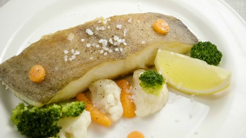 Fried halibut. A fillet of turbot on white plate with carrot, broccoli, cauliflower and slice of lemon. Slow motion. HD