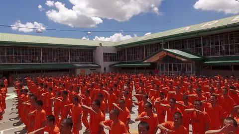 CEBU PROVINCIAL DETENTION AND REHABILITATION CENTER, CEBU, PHILIPPINES - March 2016. Cebu's dancing inmates surrounded by tourists. Choreographic practices show for tourists - aerial 4K view.