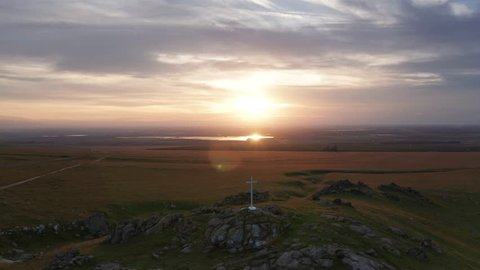 Dramatic Aerial Pull Back Shot of White Cross on Rocky Outcrop in Field, Sunset