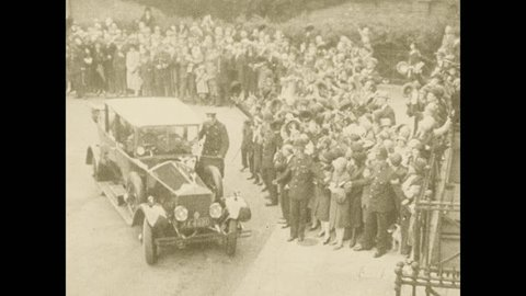 1920s: A car pulls up to a large building surrounded with crowds. The door is opened and Lindbergh gets out. Lindbergh faces the crowd.