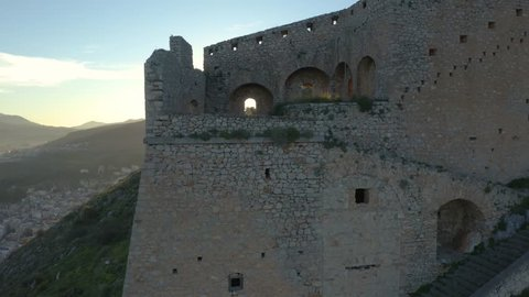 Aerial view of Palamidi castle, slow pan as sunrise peaks over horizon, Nafplio, Greece, 4k