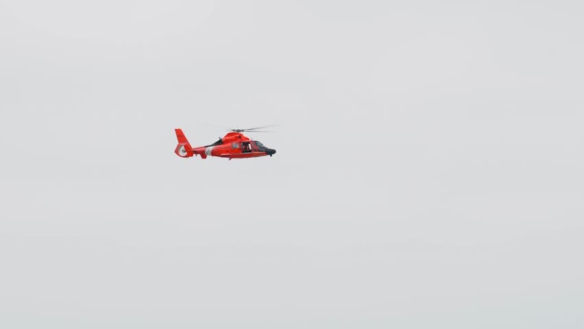 This video shows a red coast guard helicopter flying across a cloudy beach sky.