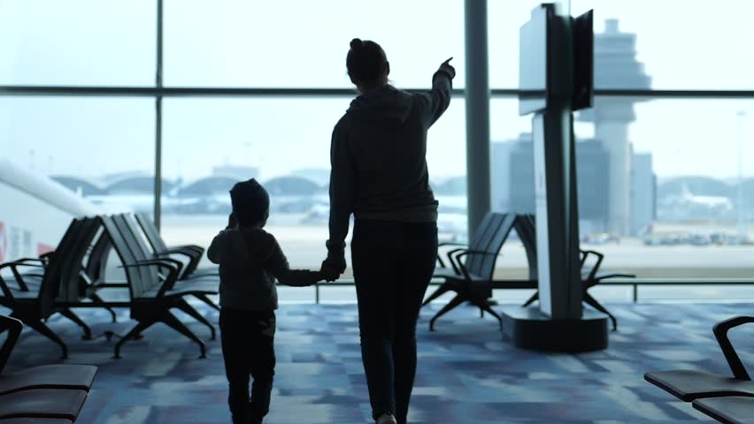 Bangkok, Thailand, 21 february 2019. Mother holds hand her son and they looking at the planes through the window in airport. Loving family waiting for fligh. slow motion. | Shutterstock HD Video #1028650499