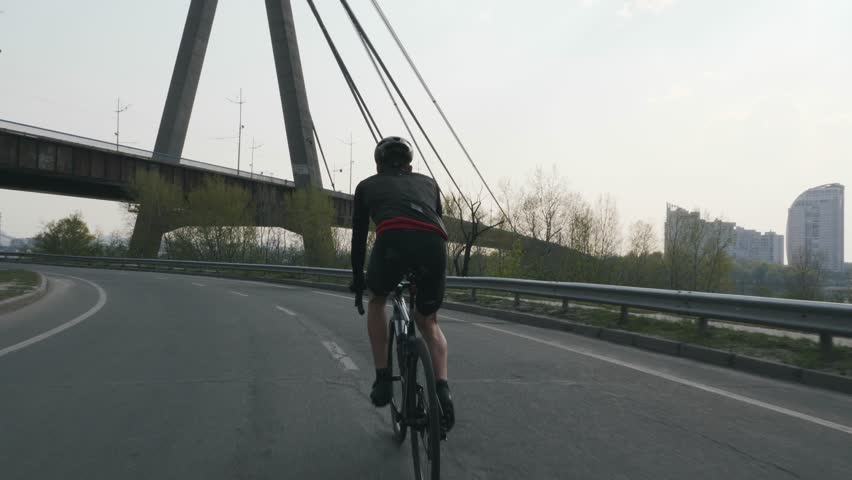 Cycling man. Male cyclist. Male triathlete riding bicycle as a part of his training schedule. He wears black outfit, helmet and sunglasses. Triathlon concept. Slow motion #1028653919