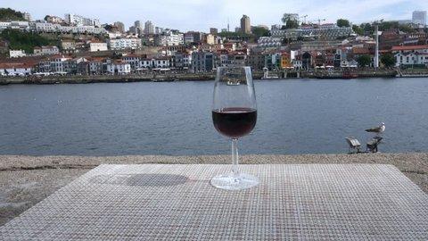 Selective focus of small glass of red Port wine overlooking Vila Nova de Gaia embankment at Cais da Ribeira on the River Douro in Porto, Portugal - 4K