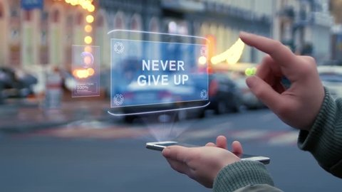 Female hands on the street interact with a HUD hologram with text Never give up. Woman uses the holographic technology of the future in the smartphone screen on the background of the evening city