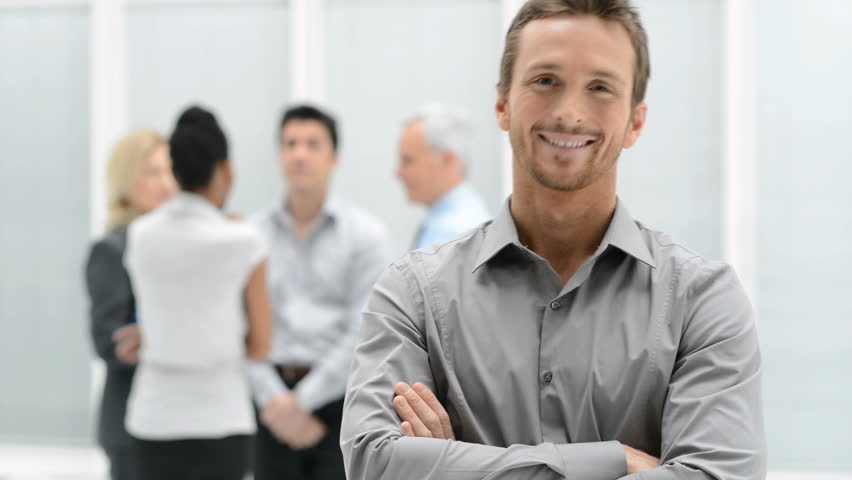 Portrait Of Young Handsome Businessman Smiling In Office. Satisfied guy with arms crossed looking at camera with his colleagues in background. Proud young man smiling in front of his business team.