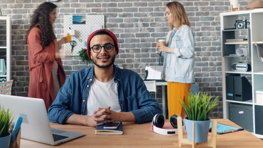 Time-lapse portrait of bearded man successful business owner smiling in office at desk while people are working in shared workspace. Millennials and business concept.