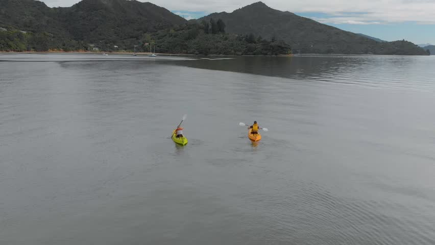 SLOWMO - Two people kayaking with yachts in background in Marlborough Sounds, New Zealand - Aerial | Shutterstock HD Video #1028789459