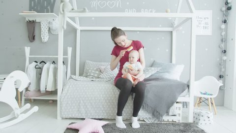 Young woman sitting on bed holding cute infant girl on knees, playful toddler daughter shoving hairbrush in mouth taking it from mom. Baby teether trying to bite comb while mother brushing her hairs.