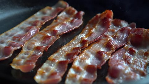 Crispy bacon, rich in fat and colour, sizzling and smoking in a hot pan.