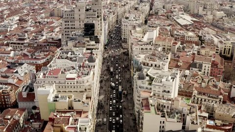 Long aerial shot of the city center Madrid. The Gran via on a busy day with citylife on the streets. People and cars are roaming around in the capital of Spain.