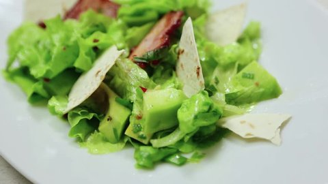 Close up view of ready prepared fresh salad made of bacon, lettuce, pita and sauce serviced in white plate. Restaurant, gourmet dish, European cuisine, delicious food. Bon apetite, appetizer