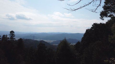 A pan shot of a beautiful mountain view on a rural trail in Japan.