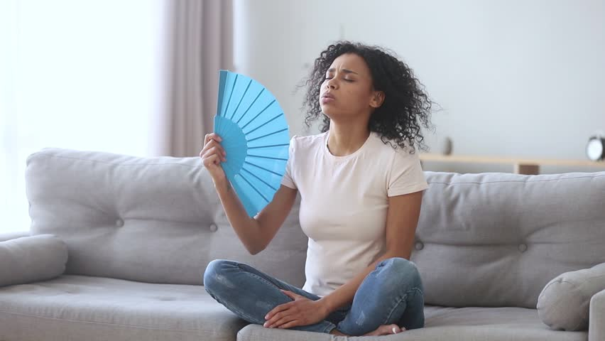 African american young woman feeling hot suffering from high temperature summer heat problem sitting on sofa at home, annoyed black girl holding waving fan sweating cooling in hot weather indoors | Shutterstock HD Video #1028899949