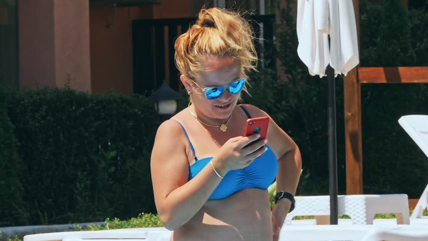 Woman sunbathing in chair by the pool and using mobile phone | Shutterstock HD Video #1028910839