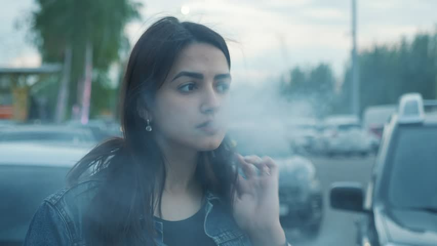 Pensive young woman vaping on the parking near the mall | Shutterstock HD Video #1028928119