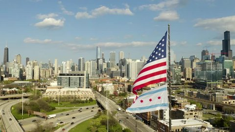 Fixed View of American and Chicago flags waving in wind with Chicago skyline and busy urban streets in background [4K]