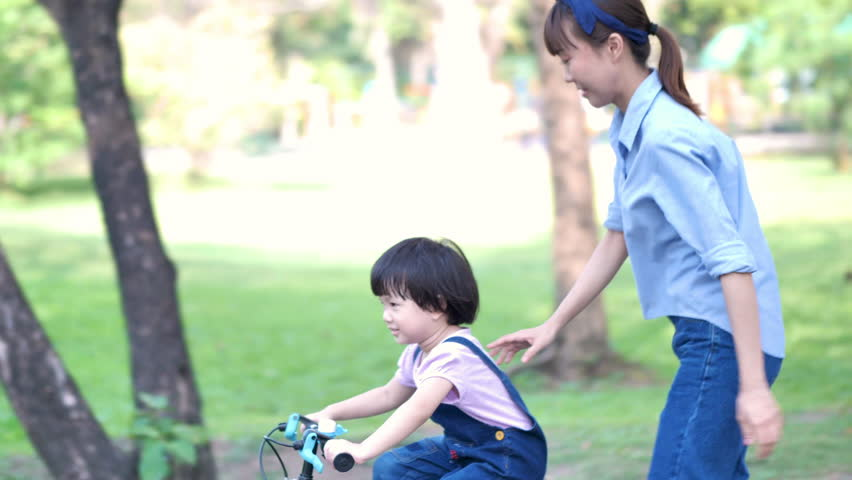Asian family with Mother teaches her daughter or children Girl to ride a bicycle having fun in nature or park and sunlight. Slow Motion | Shutterstock HD Video #1028963399