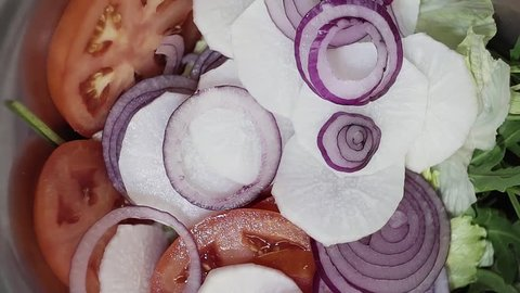 Cut slices of paprika pepper are falling on rings of fresh purple onion, slices of tomato and leaves of cabbage and arugula.