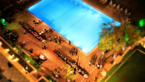 Time lapse with tilt shift miniature effect of the Hilton swimming pool in Athens, Greece during the evening, with the lights on. Buffet on the side of the pool.