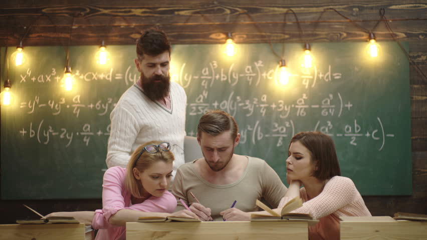 Group of students studying together in a classroom, group of four young people student with teacher in school classroom with laptop. Education, school, college and university concept
