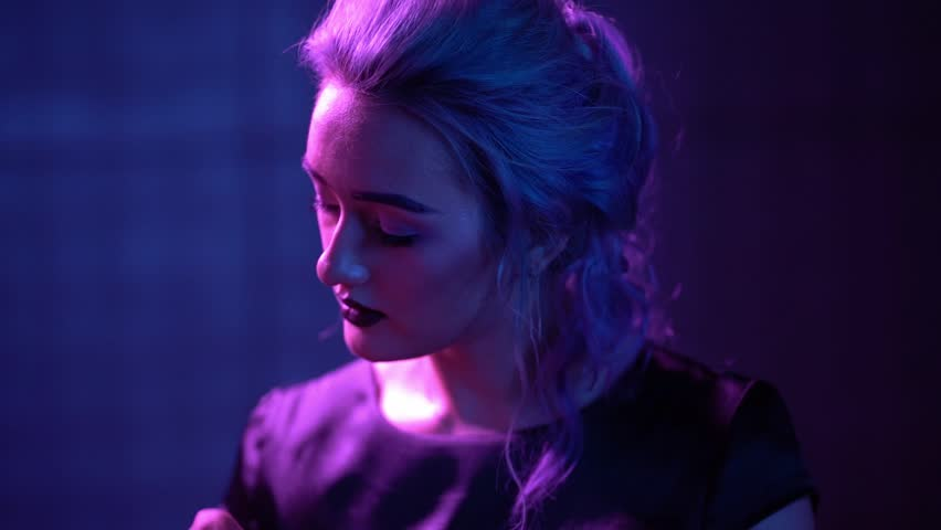 Young Blond Model is Posing in Neon. Girl has Dark Eyebrows, Red Lips and Wavy Hairstyle. Slow-Motion Fashion Video #1029010889