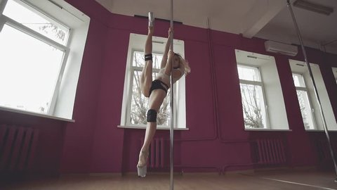 Young blonde woman performs make tricks with pole in slow motion. Young slim girl dancing near pole. Pole Dance. Wide view of beautiful woman doing poledance in studio. Exotic dance