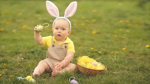 Lovely baby in an Easter bunny costume collects Easter eggs in a basket sitting on the grass in the park. Spring picnic, happy easter family