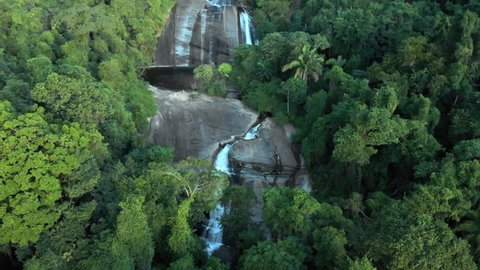 Aerial: Narrow Waterfall Cascading Down Mountain Through Jungle in Ilhabela, Brazil